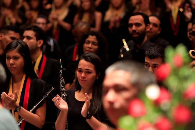 A member of the National System of Children and Youth Orchestras reacts as she applauds during the memorial service of its founder Jose Antonio Abreu in Caracas, Venezuela March 25, 2018. REUTERS/Marco Bello