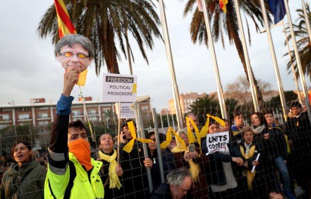 Un hombre levanta una máscara de Puigdemont durante una protesta frente al Consulado de Alemania después de que el ex presidente Carles Puigdemont fuera detenido en Alemania, durante una manifestación organizada por asociaciones independentistas en Barcelona, España, el 25 de marzo de 2018. REUTERS / Albert Gea
