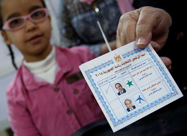 Una mujer egipcia muestra su papeleta con letrero para el presidente egipcio Abdel Fattah al-Sisi antes de emitir su voto durante el primer día de las elecciones presidenciales en un colegio electoral en El Cairo, Egipto, el 26 de marzo de 2018. REUTERS / Amr Abdallah Dalsh