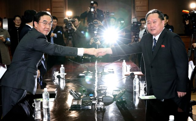 South Korean Unification Minister Cho Myoung-gyon and his North Korean counterpart Ri Son Gwon pose for photographs before their meeting at the truce village of Panmunjom, North Korea, March 29, 2018. Korea Pool/Yonhap via REUTERS ATTENTION EDITORS - THIS IMAGE HAS BEEN SUPPLIED BY A THIRD PARTY. SOUTH KOREA OUT. NO RESALES. NO ARCHIVE. TPX IMAGES OF THE DAY