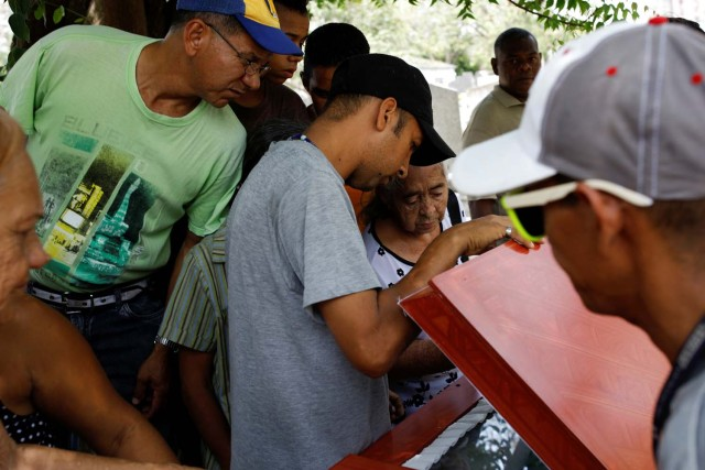 Mourners look at the coffin of Javier Rivas, one of the inmates who died during a riot and fire in the cells of the General Command of the Carabobo Police, during his funeral in Valencia, Venezuela March 29, 2018. REUTERS/Carlos Garcia Rawlins