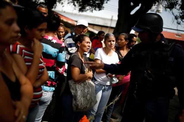 Los familiares de los presos hablan con un oficial de policía mientras esperan información luego de un motín y un incendio en las celdas del Comando General de la Policía de Carabobo en Valencia, Venezuela el 29 de marzo de 2018. REUTERS / Carlos Garcia Rawlins