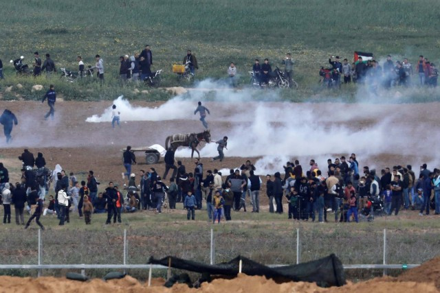 Los palestinos huyen del gas lacrimógeno en el lado de Gaza de la frontera entre Israel y Gaza, visto desde el lado israelí de la frontera, el 30 de marzo de 2018. REUTERS / Amir Cohen