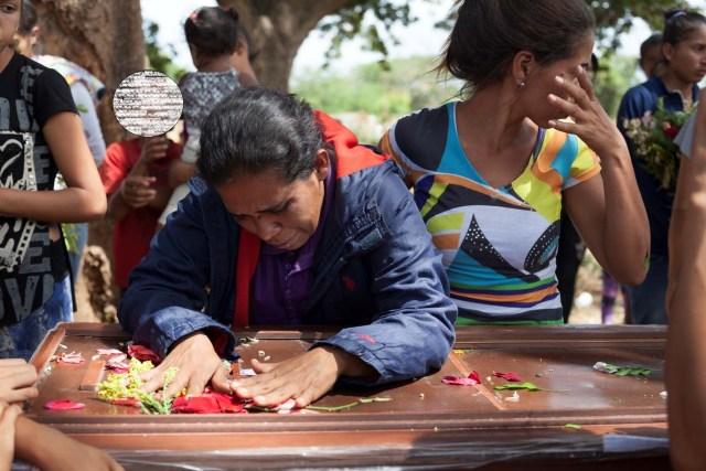 Los deudos lloran junto al ataúd de Edgar Martínez, uno de los reclusos que murió durante un motín y un incendio en las celdas del Comando General de la Policía de Carabobo, durante su funeral en un cementerio de Valencia, Venezuela, el 30 de marzo de 2018. REUTERS / Adriana Loureiro