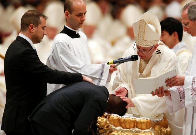 El Papa Francisco bautiza a un hombre mientras dirige la misa de vigilia de Pascua en la Basílica de San Pedro en el Vaticano, el 31 de marzo de 2018. REUTERS / Stefano Rellandini