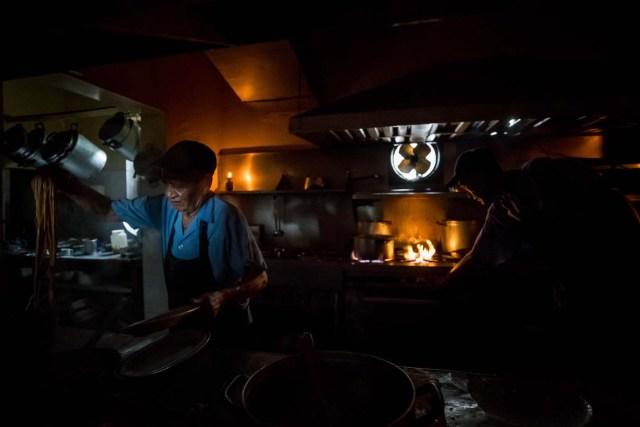 CAR207. CARACAS (VENEZUELA), 05/03/2018.- Un cocinero trabaja a oscuras en un restaurante durante una falla eléctrica hoy, lunes 5 de marzo de 2018, en Caracas (Venezuela). Un fallo eléctrico del que se desconocen por ahora los detalles ha dejado sin luz a la capital venezolana, Caracas, por tercera vez en tres meses, y 10 días después de otro apagón que afectó a una decena de estados del país petrolero. EFE/MIGUEL GUTIÉRREZ