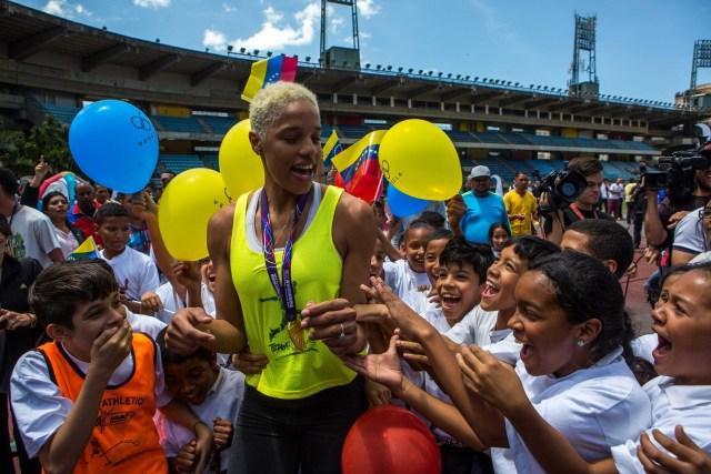 """CAR01. CARACAS, 08/03/2018.- La atleta de triple salto venezolana Yulimar Rojas (c) saluda a un grupo de niños hoy, jueves 8 de marzo de 2018, durante un encuentro con la prensa después de ganar el campeonato mundial de triple salto bajo techo, en Caracas (Venezuela). La bicampeona mundial de triple salto, la venezolana Yulimar Rojas, felicitó hoy a su rival y compañera de entrenamiento, Ana Peleteiro, de quien dijo """"encontró la luz"""" con su desempeño en el último campeonato mundial de atletismo, en el que la española se alzó con un histórico bronce. EFE/CRISTIAN HERNÁNDEZ"""
