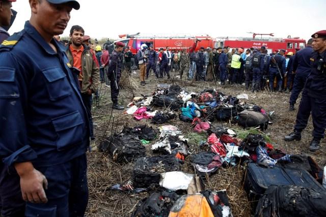 EPA6008. KATMANDÚ (NEPAL), 12/03/2018.- Miembros de los servicios de emergencia rodean parte del equipaje recuperado del avión que se estrelló en el aeropuerto de Katmandú (Nepal) hoy, 12 de marzo de 2018. Al menos 49 personas han muerto y 22 resultaron heridas en el accidente del avión de la línea bangladeshí US-Bangla con 67 pasajeros y 4 miembros de la tripulación a bordo. EFE/ Narendra Shrestha