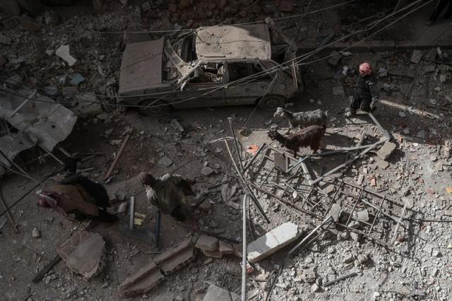 Varias personas caminan por un área destrozada tras un bombardeo en Duma (Siria) hoy, 19 de marzo de 2018. Según medios de comunicación, al menos nueve personas han muerto en el bombardeo que supuestamente fue llevado a cabo por las fuerzas leales al gobierno de Bachar Al Asad. EFE/ Mohammed Badra