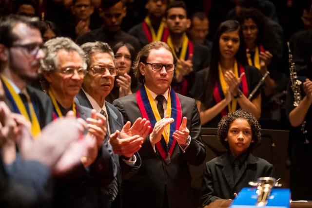 CAR014. CARACAS (VENEZUELA), 25/03/2018.- El director musical venezolano Christian Vásquez participa en los actos conmemorativos durante el velorio de Jose Antonio Abreu hoy, domingo 25 de marzo del 2018, en Caracas (Venezuela). El músico y economista José Antonio Abreu, premio Príncipe de Asturias de las Artes por el reconocido programa de música El Sistema Nacional de Orquestas de Venezuela, murió ayer a los 79 años. El presidente de Venezuela, Nicolás Maduro, decretó tres días de duelo nacional por su muerte. EFE/Miguel Gutiérrez