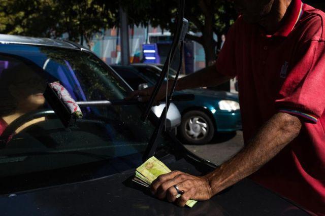 Un asistente de PDVSA tiene una pila de billetes de Bolívar mientras ayuda a un cliente en una estación de servicio en Caracas. Fotógrafo: Wil Riera / Bloomberg