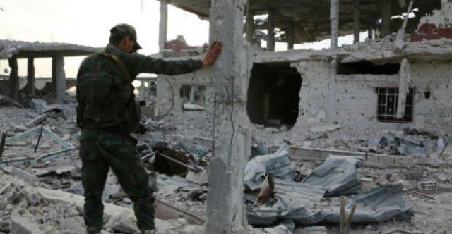 Un miembro de las fuerzas gubernamentales sirias observa la destrucción en Al Shifoniya el 4 de marzod e 2018, mientras continúa el avance en la región rebelde de Guta Orienta. AFP
