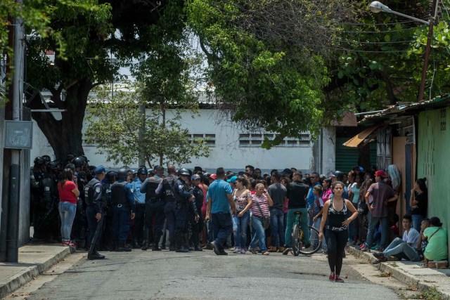 VALENCIA (VENEZUELA), 28/03/2018.- Un grupo de familiares de presos protesta ante miembros de la Policía hoy, miércoles 28 de marzo de 2018, en las inmediaciones del centro de reclusión de la Policía Estatal de Carabobo (centro) en Valencia (Venezuela). Un motín en el centro de reclusión de la Policía de Carabobo (centro) de Venezuela dejó hoy cinco reclusos muertos y dos policías heridos, según medios locales. EFE/Miguel Gutiérrez