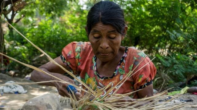 Una anciana Yukpa está tejiendo una canasta que se vende para ayudar a la comunidad (Bram Ebus / Al Jazeera)