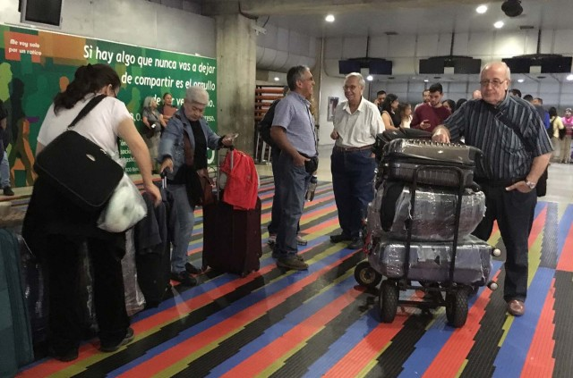 People remain stranded at Caracas' international airport on April 6, 2018 after Venezuela suspended flights of Panama's Copa Airlines in an escalating diplomatic row. Panama on April 5 ordered Venezuela's ambassador out and recalled its own envoy to the country as Caracas imposed sanctions on senior Panamanian officials and suspended flights in an escalating diplomatic row. At issue is Panama's alignment with other Latin American countries as well as the European Union, Canada and the United States that have taken measures against President Nicolas Maduro's and his government on the grounds that he is undemocratically tightening his hold on power. / AFP PHOTO / Federico PARRA