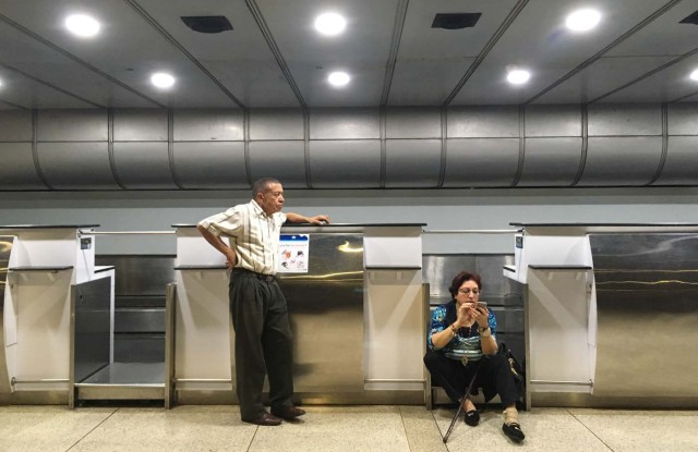 People wait at the counters of Panama's Copa Airlines at Caracas' international airport on April 6, 2018 after Venezuela suspended the company's flights in an escalating diplomatic row. Panama on April 5 ordered Venezuela's ambassador out and recalled its own envoy to the country as Caracas imposed sanctions on senior Panamanian officials and suspended flights in an escalating diplomatic row. At issue is Panama's alignment with other Latin American countries as well as the European Union, Canada and the United States that have taken measures against President Nicolas Maduro's and his government on the grounds that he is undemocratically tightening his hold on power. / AFP PHOTO / Federico PARRA