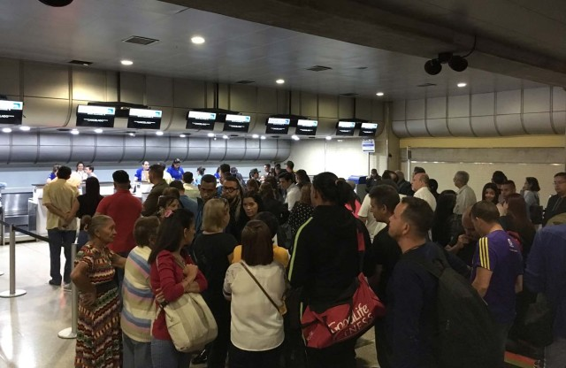 People queue at counters of Panama's Copa Airlines at Caracas' international airport on April 6, 2018 after Venezuela suspended the company's flights in an escalating diplomatic row. Panama on April 5 ordered Venezuela's ambassador out and recalled its own envoy to the country as Caracas imposed sanctions on senior Panamanian officials and suspended flights in an escalating diplomatic row. At issue is Panama's alignment with other Latin American countries as well as the European Union, Canada and the United States that have taken measures against President Nicolas Maduro's and his government on the grounds that he is undemocratically tightening his hold on power. / AFP PHOTO / Federico PARRA