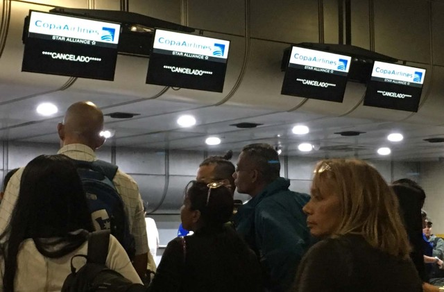 Screens of Panama's Copa Airlines announce flight have been cancelled at Caracas' international airport on April 6, 2018 after Venezuela suspended flights of the company in an escalating diplomatic row. Panama on April 5 ordered Venezuela's ambassador out and recalled its own envoy to the country as Caracas imposed sanctions on senior Panamanian officials and suspended flights in an escalating diplomatic row. At issue is Panama's alignment with other Latin American countries as well as the European Union, Canada and the United States that have taken measures against President Nicolas Maduro's and his government on the grounds that he is undemocratically tightening his hold on power. / AFP PHOTO / Federico PARRA