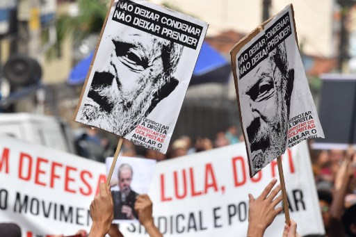 """Los partidarios del ex presidente brasileño (2003-2011) Luiz Inácio Lula da Silva sostienen pancartas que dicen """"No dejen que lo sentencien. No dejen que lo detuven"""" mientras esperan afuera del edificio sindical de los trabajadores metalúrgicos en Sao Bernardo do Campo, en el área metropolitana de Sao Paulo, Brasil, el 7 de abril de 2018. El encarcelamiento inminente del Lula de Brasil puede haber asestado un golpe devastador a la izquierda del país, pero también ha sacudido a sus rivales políticos de la derecha, la mayoría de los cuales también están siendo investigados por corrupción. Ha habido un silencio ensordecedor en torno al arresto de Luiz Inácio Lula da Silva, quien enfrenta 12 años tras las rejas por aceptar sobornos y lavado de dinero, especialmente dado que su desaparición política posiblemente elimine al principal favorito en las elecciones presidenciales de octubre."""