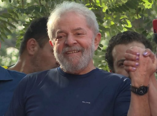 This screen grab shows Brazilian ex-president (2003-2011) Luiz Inacio Lula da Silva waving to supporters at the metalworkers' union building in Sao Bernardo do Campo, in metropolitan Sao Paulo, Brazil, on April 7, 2018. Lula da Silva attended a mass for his late wife Marisa Leticia Saturday at the metalworkers' union building, where he remained entrenched for two days while his lawyers negotiated his surrendering to police. Lula is facing 12 years behind bars for taking bribes and money laundering.  / AFP PHOTO / Carlos Reyes