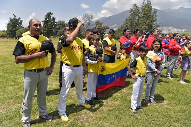 Venezuelan immigrants attend the inauguration of the Pichincha League Softball Championship, at Parque Bicentenario, in Quito on March 18, 2018. The increase in the number of Venezuelan immigrants in Ecuador leaded to growth of the softball league from four to 16 teams in the last years, with some 450 players in total. / AFP PHOTO / Rodrigo BUENDIA / TO GO WITH AFP STORY BY PAOLA LOPEZ