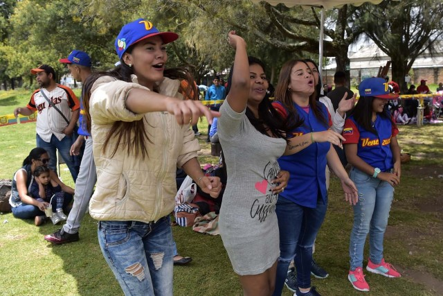 Venezuelan immigrants cheer for their team during the inauguration of the Pichincha League Softball Championship, at Parque Bicentenario, in Quito on March 18, 2018. The increase in the number of Venezuelan immigrants in Ecuador leaded to growth of the softball league from four to 16 teams in the last years, with some 450 players in total. / AFP PHOTO / Rodrigo BUENDIA / TO GO WITH AFP STORY BY PAOLA LOPEZ