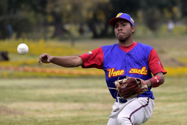 A Venezuelan immigrant plays softball during the inauguration of the Pichincha League Softball Championship, at Parque Bicentenario, in Quito on March 18, 2018. The increase in the number of Venezuelan immigrants in Ecuador leaded to growth of the softball league from four to 16 teams in the last years, with some 450 players in total. / AFP PHOTO / Rodrigo BUENDIA / TO GO WITH AFP STORY BY PAOLA LOPEZ