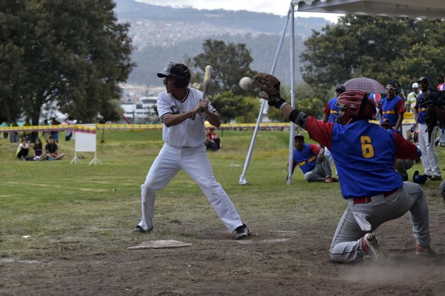 Venezuelan immigrants play softball during the inauguration of the Pichincha League Softball Championship, at Parque Bicentenario, in Quito on March 18, 2018. The increase in the number of Venezuelan immigrants in Ecuador leaded to growth of the softball league from four to 16 teams in the last years, with some 450 players in total. / AFP PHOTO / Rodrigo BUENDIA / TO GO WITH AFP STORY BY PAOLA LOPEZ