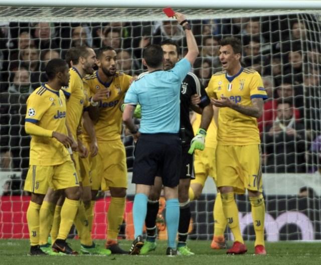 El árbitro inglés Michael Oliver (4L) leyó una tarjeta al portero italiano Juventus Gianluigi Buffon (2R) durante el partido de fútbol de cuartos de final de la UEFA Champions League entre Real Madrid CF y Juventus FC en el estadio Santiago Bernabéu de Madrid el 11 de abril , 2018.  CURTO DE LA TORRE / AFP