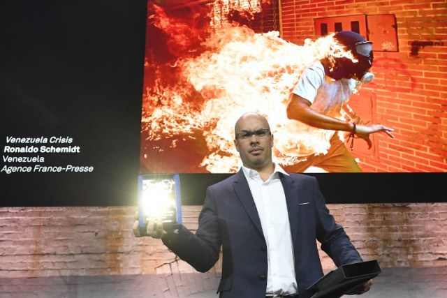 Venezualan AFP photographer Ronaldo Schemidt holds his trophy in Amsterdam on April 12, 2018 during the 2018 World Press Photo (WPP) award ceremony after being awarded with both picture of the Year 2018 award and 1st prize in the Spot News Singles category for the picture projected above taken on May 3, 2017 of a demonstrator catching fire during clashes with riot police within a protest against Venezuelan President in Caracas. / AFP PHOTO / EMMANUEL DUNAND