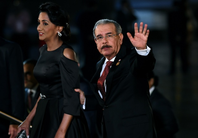 Dominican Republic's President Danilo Medina (R) waves next to his wife Candida Montilla, upon arrival at the National Theatre in Lima to attend the Eighth Summit of the Americas inauguration ceremony, on April 13, 2018. / AFP PHOTO / CRIS BOURONCLE