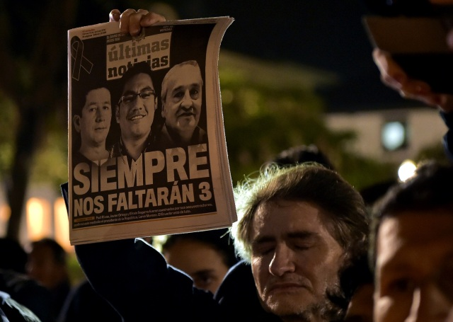 A man holds a newspaper during a tribute to Ecuadorean murdered journalist Javier Ortega, photographer Paul Rivas and their driver Efrain Segarra, in front of Metropolitan Cathedral, in Quito on April 13, 2018. The three members of an Ecuadoran journalist team who died in captivity after being abducted by a Colombian rebel group were following a story on violence that ended up costing their lives. / AFP PHOTO / RODRIGO BUENDIA