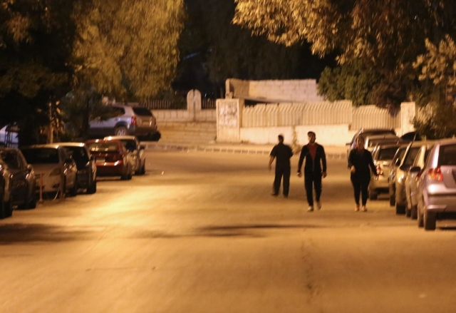 A photo taken in the early hours of April 14, 2018 shows pedestrians walking in an empty street before the daybreak Muslim prayer in Damascus' Mazze neighbourhood after the US, France, and Britain launched a joint operation against the Syrian government. Western strikes early Saturday hit Syrian military bases and research centres in and around the capital and the country's centre, a monitor said, as the US, France, and Britain announced a joint operation. / AFP PHOTO / STRINGER