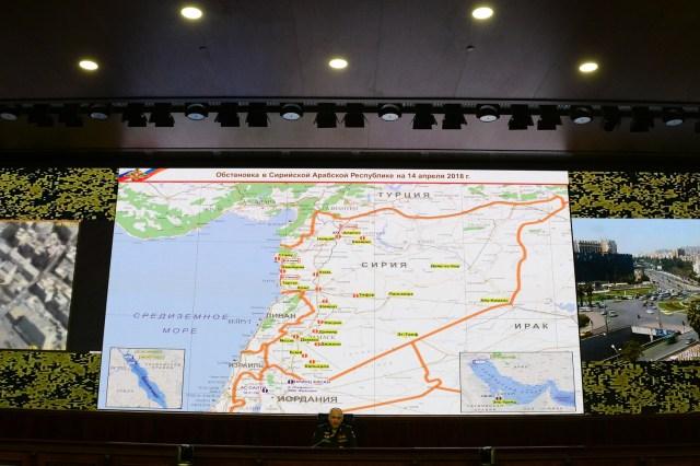 El alto oficial militar de Rusia Sergei Rudskoi se sienta debajo de un mapa de Siria proyectado durante una sesión informativa en la sede del Ministerio de Defensa ruso en Moscú el 14 de abril de 2018. El ejército ruso dijo el 14 de abril de 2018 que los aliados occidentales dispararon 103 misiles de crucero, incluidos los misiles Tomahawk, pero que los sistemas de defensa antiaérea sirios interceptaron a 71 de ellos. Estados Unidos, Gran Bretaña y Francia llevaron a cabo ataques conjuntos durante la noche del 14 de abril contra el régimen sirio de Bashar al-Assad en respuesta a presuntos ataques con armas químicas. / AFP PHOTO / Kirill KUDRYAVTSEV