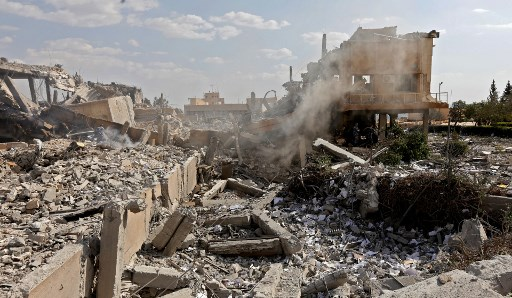"This picture taken on April 14, 2018 shows the wreckage of a building described as part of the Scientific Studies and Research Centre (SSRC) compound in the Barzeh district, north of Damascus, during a press tour organised by the Syrian information ministry. The United States, Britain and France launched strikes against Syrian President Bashar al-Assad's regime early on April 14 in response to an alleged chemical weapons attack after mulling military action for nearly a week. Syrian state news agency SANA reported several missiles hit a research centre in Barzeh, north of Damascus, ""destroying a building that included scientific labs and a training centre"". / AFP PHOTO / LOUAI BESHARA"