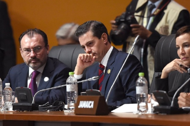 Mexican President Enrique Pena Nieto (C) attends the plenary session of the Eighth Americas Summit in Lima, on April 14, 2018. US strikes on Syria overshadowed the Americas Summit, which ends Saturday condemning corruption and calling for more sanctions on the Venezuelan government. / AFP PHOTO / Luka GONZALES