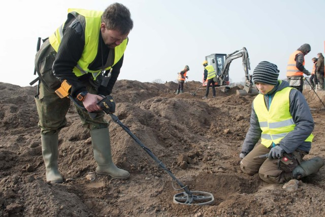 """Amateur archaeologist Rene Schoen (L) and 13-year-old student Luca Malaschnichenko look for a treasure with a metal detector in Schaprode, northern Germany on April 13, 2018. The 13-year-old boy and the hobby archaeologist have unearthed a """"significant"""" trove in Germany which may have belonged to the legendary Danish king Harald Bluetooth who brought Christianity to Denmark. A dig covering 400 square metres (4,300 square feet) that finally started over the weekend by the regional archaeology service has since uncovered a trove believed linked to the Danish king who reigned from around 958 to 986. Braided necklaces, pearls, brooches, a Thor's hammer, rings and up to 600 chipped coins were found, including more than 100 that date back to Bluetooth's era. / AFP PHOTO / dpa / Stefan Sauer / Germany OUT"""