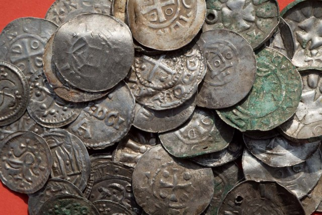 """Saxon, Ottonian, Danish and Byzantine coins are pictured on a table in Schaprode, northern Germany on April 13, 2018. A 13-year-old boy and a hobby archaeologist have unearthed a """"significant"""" trove in Germany which may have belonged to the legendary Danish king Harald Bluetooth who brought Christianity to Denmark. A dig covering 400 square metres (4,300 square feet) that finally started over the weekend by the regional archaeology service has since uncovered a trove believed linked to the Danish king who reigned from around 958 to 986. Braided necklaces, pearls, brooches, a Thor's hammer, rings and up to 600 chipped coins were found, including more than 100 that date back to Bluetooth's era. / AFP PHOTO / dpa / Stefan Sauer / Germany OUT"""