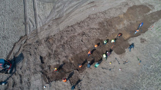 """This aerial picture taken with a drone on April 13, 2018 shows archaeologists looking for a treasure in Schaprode, northern Germany. A 13-year-old boy and a hobby archaeologist have unearthed a """"significant"""" trove in Germany which may have belonged to the legendary Danish king Harald Bluetooth who brought Christianity to Denmark. A dig covering 400 square metres (4,300 square feet) that finally started over the weekend by the regional archaeology service has since uncovered a trove believed linked to the Danish king who reigned from around 958 to 986. Braided necklaces, pearls, brooches, a Thor's hammer, rings and up to 600 chipped coins were found, including more than 100 that date back to Bluetooth's era. / AFP PHOTO / dpa / Stefan Sauer / Germany OUT"""