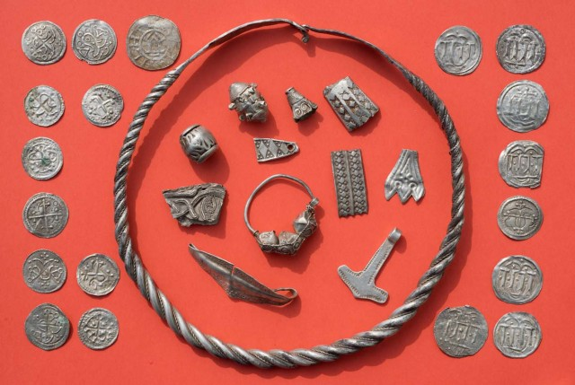 """Parts of the silver treasure are pictured on a table in Schaprode, northern Germany on April 13, 2018. A 13-year-old boy and a hobby archaeologist have unearthed a """"significant"""" trove in Germany which may have belonged to the legendary Danish king Harald Bluetooth who brought Christianity to Denmark. A dig covering 400 square metres (4,300 square feet) that finally started over the weekend by the regional archaeology service has since uncovered a trove believed linked to the Danish king who reigned from around 958 to 986. Braided necklaces, pearls, brooches, a Thor's hammer, rings and up to 600 chipped coins were found, including more than 100 that date back to Bluetooth's era. / AFP PHOTO / dpa / Stefan Sauer / Germany OUT"""