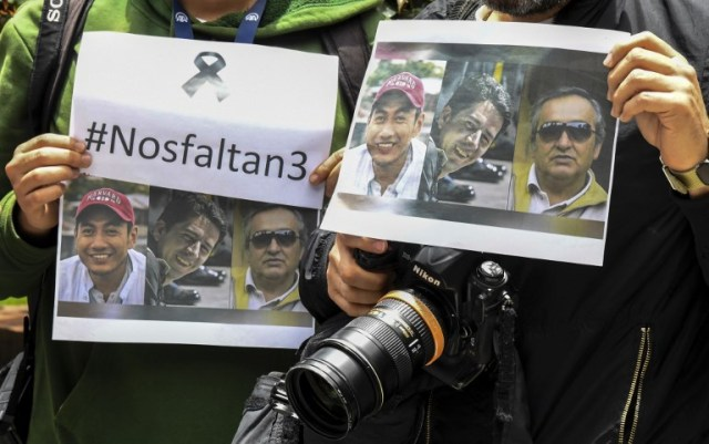 Colombian journalists gather in front of the Ecuadorean embassy in Bogota to protest against the murder of Ecuadorean journalist Javier Ortega, photographer Paul Rivas and their driver Efrain Segarra, on April 16 2018. The three members of an Ecuadoran journalist team who were kidnapped and killed in captivity after being abducted by a Colombian rebel group were following a story on violence that ended up costing their lives.  / AFP PHOTO / Luis ACOSTA