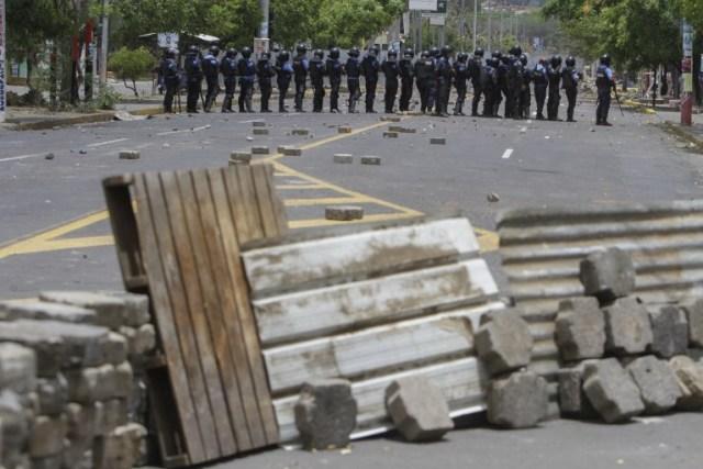 Agentes de la policía antidisturbios chocan con estudiantes frente a la Universidad de Ingeniería durante una protesta contra las reformas del gobierno en el Instituto de Seguridad Social (INSS) en Managua el 20 de abril de 2018. Un manifestante y un policía fueron asesinados en la capital nicaragüense Managua después de las manifestaciones La reforma de las pensiones se tornó violenta la noche del jueves, dijeron las autoridades. Las muertes se produjeron después de las protestas de opositores y partidarios de una nueva ley, que aumenta las contribuciones de los empleadores y los empleados, mientras que reduce el monto total de las pensiones en un cinco por ciento, sacudió la capital por segundo día consecutivo.  INTI OCON / AFP