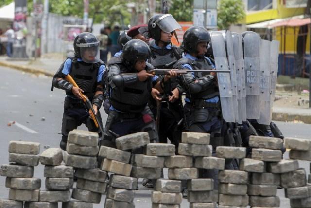 Agentes de la policía antidisturbios chocan con estudiantes frente a la Universidad de Ingeniería durante una protesta contra las reformas del gobierno en el Instituto de Seguridad Social (INSS) en Managua el 20 de abril de 2018. Un manifestante y un policía fueron asesinados en la capital nicaragüense, Managua, luego de que las manifestaciones por la reforma de las pensiones se volvieran violentas el jueves por la noche, dijeron las autoridades. Las muertes se produjeron después de las protestas de opositores y partidarios de una nueva ley, que aumenta las contribuciones de los empleadores y los empleados, mientras que reduce el monto total de las pensiones en un cinco por ciento, sacudió la capital por segundo día consecutivo. / AFP PHOTO / INTI OCON