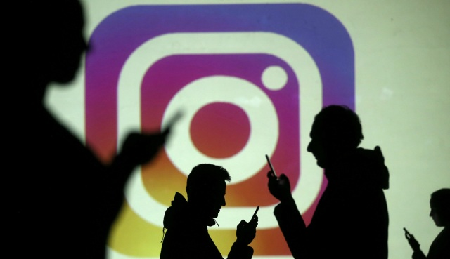 REFILE - CLARIFYING CAPTION Silhouettes of mobile users are seen next to a screen projection of Instagram logo in this picture illustration taken March 28, 2018.  REUTERS/Dado Ruvic/Illustration