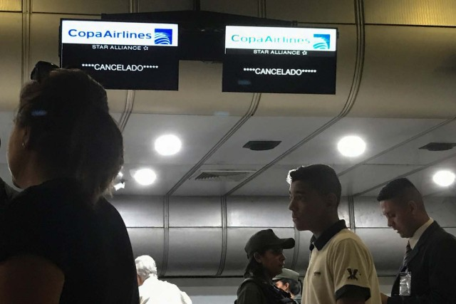 "Screens that read ""Cancelled"" hang above counters of Copa Airlines at the Simon Bolivar airport in Caracas, Venezuela April 6, 2018. REUTERS/Marco Bello"
