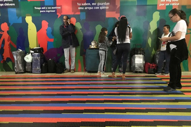 People wait by a counter of Copa Airlines, at the Simon Bolivar airport in Caracas, Venezuela April 6, 2018. REUTERS/Marco Bello