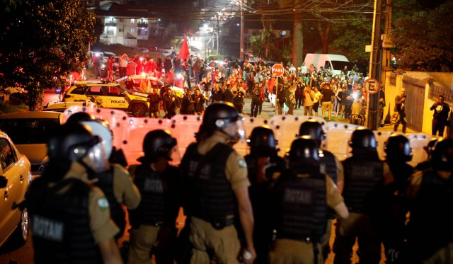 Supporters of former Brazilian President Luiz Inacio Lula da Silva are seen behind riot police in front of the Federal Police headquarters, in Curitiba, Brazil, April 7, 2018. REUTERS/Rodolfo Buhrer
