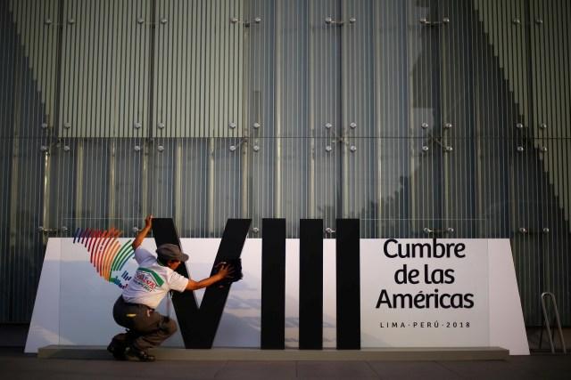 Una mujer limpia la insignia de la VIII Cumbre de las América antes de su inicio en Lima, Perú, 10 de abril de 2018. REUTERS/Ivan Alvarado - RC11B161FBE0
