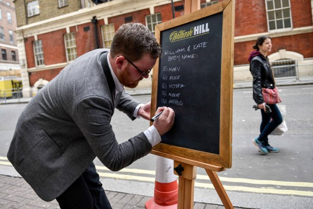 Joe Crilly, a spokesperson from the bookmaker William Hill, writes the names and betting odds for the third royal baby of Britain's Prince William and Catherine, Duchess of Cambridge, on a board outside the Lindo Wing St Mary's Hospital in west London, Britain, April 13, 2018. REUTERS/Peter Summers