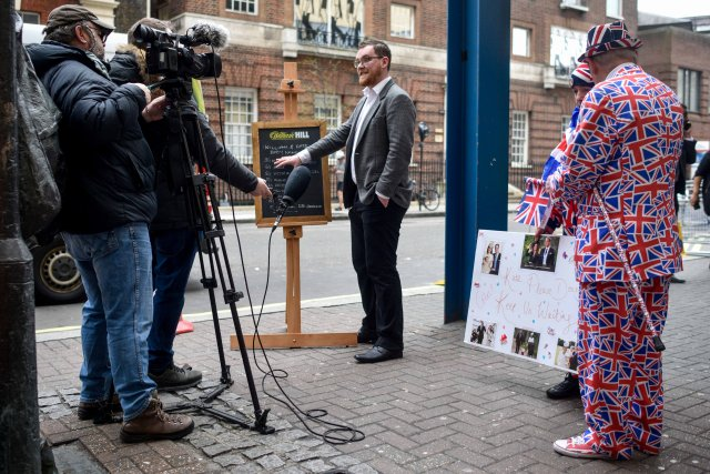 Joe Crilly, a spokesperson from the bookmaker William Hill, is interviewed by a televsion crew as he writes the names and betting odds for the third royal baby of Britain's Prince William and Catherine, Duchess of Cambridge, on a board outside the Lindo Wing St Mary's Hospital in west London, Britain, April 13, 2018. REUTERS/Peter Summers